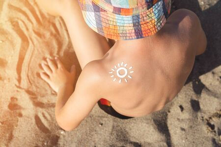 Sun lotion on taned kid's shoulder, close up view. Sun protection on the beach. Kid's sun protection.