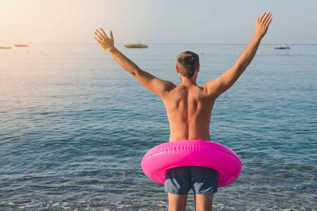 Happy man in pink with a big inflatable ring on the sea beach in summer sunny day. Back view.