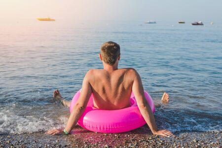Happy man with big pink inflatable ring on the sea beach in summer sunny day. Back view. Imagens