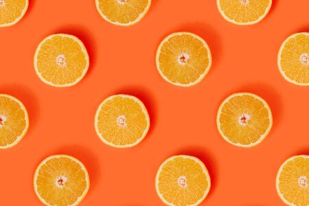 Orange slices pattern on bright orange background. Minimal flat lay concept. Top view.