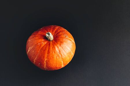Orange pumpkin with hard shadow on black background. Halloween concept. Imagens - 147916707