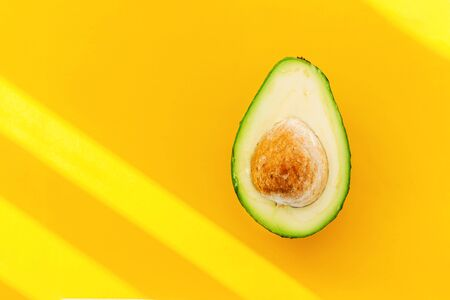 Half ripe avocado on bright yellow background with copy space. Minimalism concept.