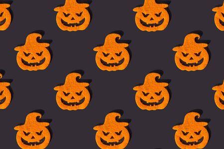 Creative pattern of orange halloween pumpkins on dark background. Top view.