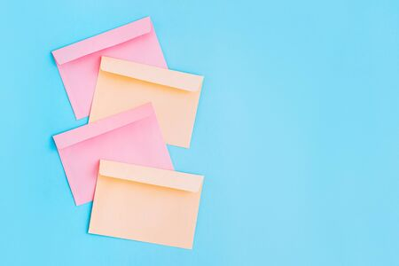 Colorful correspondence envelopes on blue background with copy space. Top view.