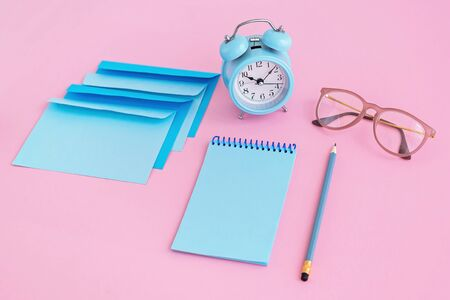 Blue correspondence envelopes, clock and notebook on pink background with copy space. Back to school or work concept. Top view.