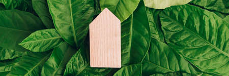 Banner with miniature wooden house on green leaves. Eco-friendly and energy efficient house concept.