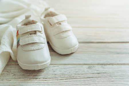 Baby white shoes and warm blanket on wooden background.