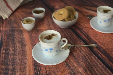 Two small cups of coffee with milk, a small white bowl with butter cookies, two other smaller bowls, one with brown sugar and the oher with cinnamon, on wooden table.