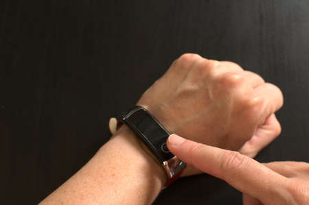 Close-up of woman using smart bracelet, woman hand.