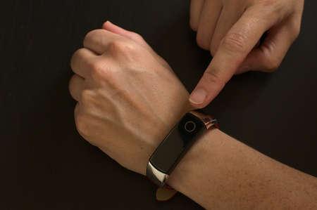 Close-up of woman using smart bracelet, woman hand
