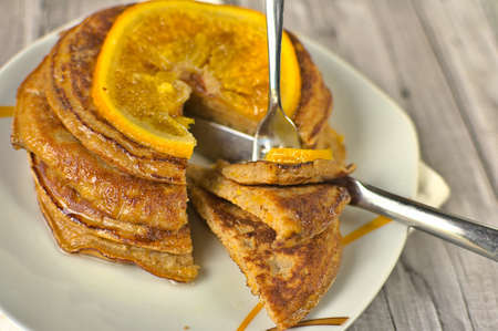 Close up of pumpkin pancake with orange, a piece cut and pierced with a fork