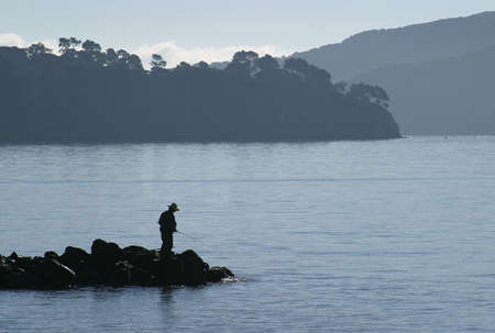 Silhouette of man fishing off jetty in bay.