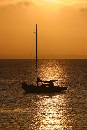 Sailboat at anchor on bay in golden morning light.