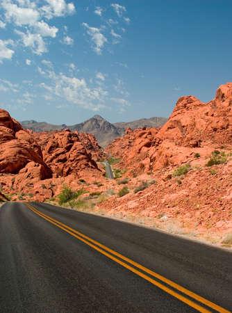 route desert: Le sud-ouest du d�sert de la route serpentant � travers des formations rocheuses rouge.  Banque d'images