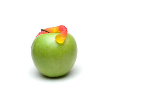 A candy worm on a green apple isolated on a white background. Stock Photo - 506047