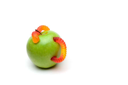 A candy worm ridden green apple isolated on a white background. photo