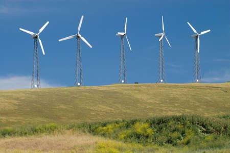 Five wind turbines generating green wind energy.