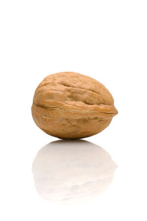 A single walnut and its reflection against a white background.