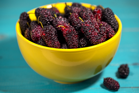 black mulberries in bowl Фото со стока