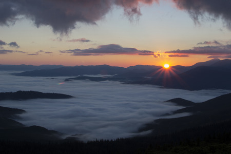 Sunrise in the mountains above the clouds photo