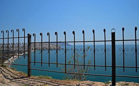 Black metal fence near the blue sea photo
