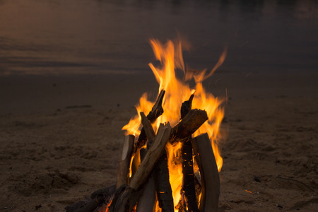 Bonfire on the sandy beach after sunset photo