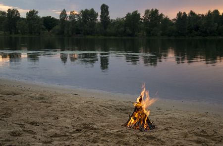 Bonfire on the bank of the river at sunset time photo
