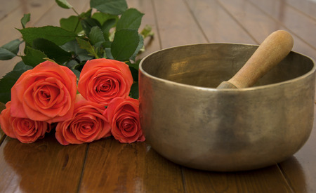 Singing bowl on wooden surface near the roses photo