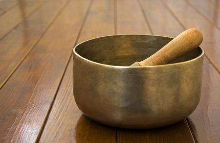 singing bowl: Metal singing bowl on a wooden surface