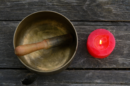 singing bowls: Singing Bowl and burning red candle on a wooden background