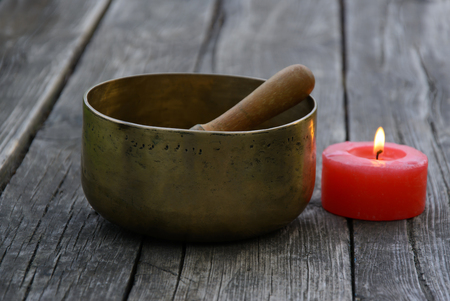 singing bowl: Singing Bowl and burning red candle on a wooden background