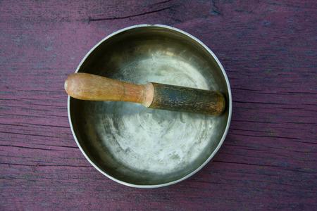 singing bowl massage: Metal singing bowl on a wooden surface