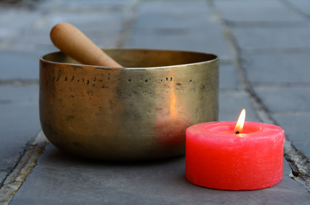 singing bowl: Singing Bowl and burning red candle on the stone floor Stock Photo
