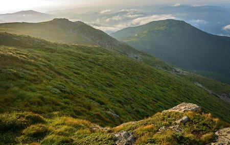 green ridge: Green ridge with rocks and clouds at sunrise
