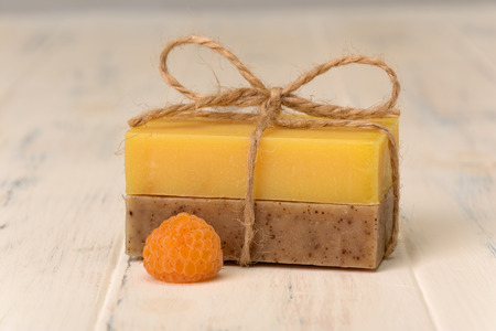 wicker bar: Two bar of soap and one yellow berry raspberry Stock Photo