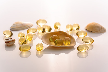 Fish oil capsules and shells on white background