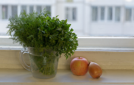 bunches: Bunches of dill and parsley in a jar on the windowsill