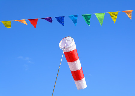 Wind cone and colored flags on a blue sky background