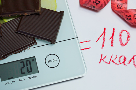 calorific: Chocolate, scales and calories. The concept of proper nutrition Stock Photo