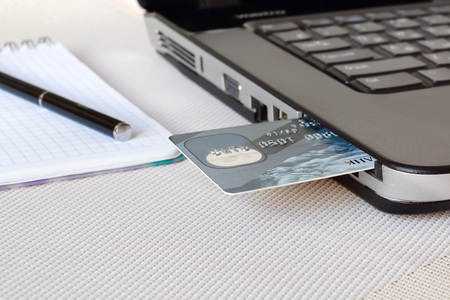internet terminal: Credit card inserted in laptop. concept shopping on the Internet.