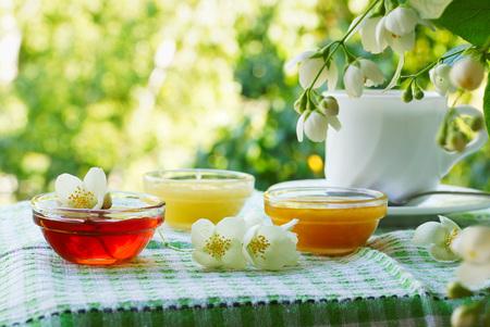 jasmine bush: Three bowls of honey and cup of tea on the table under the jasmine bush.