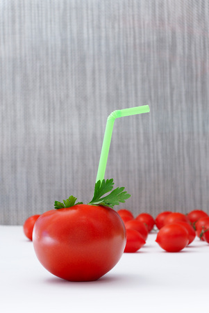 thrust: tomato juice.Straws for drinks thrust in tomato. small tomatoes in the background. Stock Photo