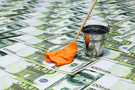 Laundering of money. Banknotes, a bucket of water and a mop with a rag