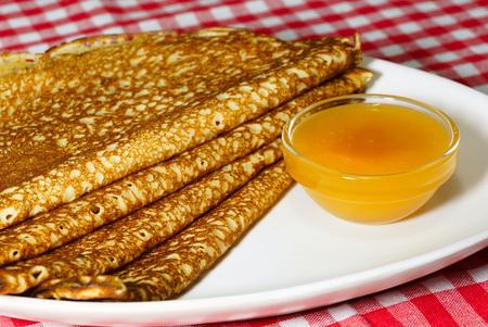 pancake week: Pancake week. Pancakes and bowl of honey on a white plate Stock Photo