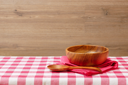 free dish: Empty wooden bowl and spoon on a red checkered tablecloth. Wooden background. Rustic style. Free space for creativity.