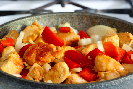 second meal: Fried chicken with bell peppers and onions in the frying pan. Cooking.