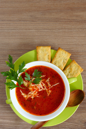 gazpacho: Tomato soup in a green cup on a wooden table. Top view