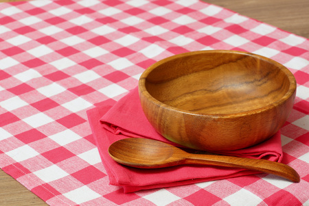free dish: Empty wooden bowl and spoon on a red checkered tablecloth. Stock Photo