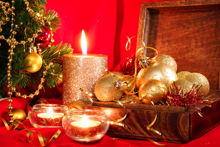 Golden Christmas balls in a wooden box and candles. New Year composition