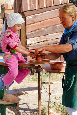 sudak: SUDAK, CRIMEA- September 2016. A women potter teaches a little girl pottery art.